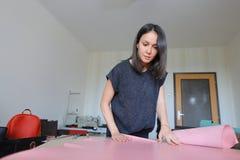 Muchacha que usa el permiso por maternidad para hacer los accesorios de cuero Fotografía de archivo libre de regalías