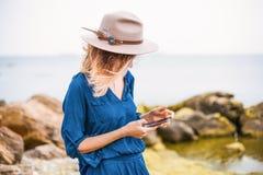 Muchacha que usa el teléfono, cierre encima del retrato de la mujer joven en el sombrero marrón al aire libre divertirse en el ma Imágenes de archivo libres de regalías