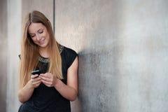 Muchacha que usa el teléfono elegante Foto de archivo libre de regalías