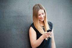 Muchacha que usa el teléfono elegante Imagenes de archivo