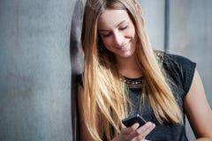 Muchacha que usa el teléfono elegante Fotos de archivo libres de regalías