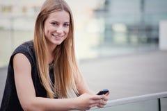 Muchacha que usa el teléfono elegante Imagen de archivo libre de regalías