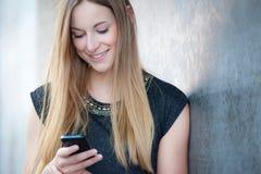 Muchacha que usa el teléfono elegante Imagen de archivo