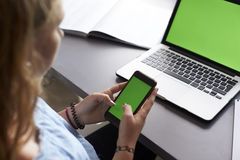Muchacha que usa el teléfono en el escritorio en su dormitorio, sobre la opinión del hombro Fotografía de archivo libre de regalías