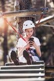 Muchacha que usa el teléfono en parque de la aventura Imagenes de archivo