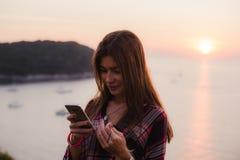 Muchacha que usa el teléfono móvil cerca del mar en salida del sol o puesta del sol Imagenes de archivo