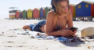 Muchacha que usa el teléfono móvil en la playa 4k almacen de video