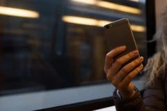 Muchacha que usa el teléfono móvil en tren Fotos de archivo