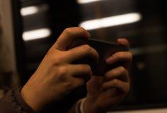 Muchacha que usa el teléfono móvil en tren Foto de archivo libre de regalías