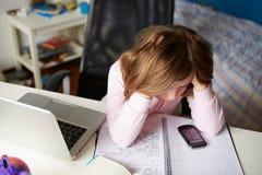 Muchacha que usa el teléfono móvil en vez de estudiar en dormitorio Imagenes de archivo
