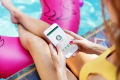 Muchacha que usa el teléfono móvil por la piscina Foto de archivo