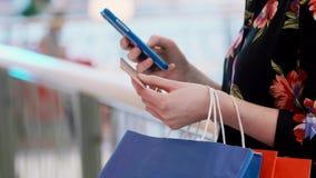 Muchacha que usa el teléfono móvil y la tarjeta de crédito durante compras en línea metrajes