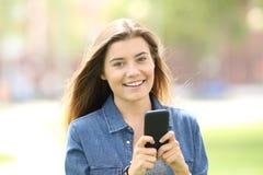 Muchacha que usa el teléfono móvil y mirándole Imagenes de archivo