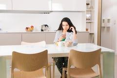 Muchacha que usa el teléfono mientras que desayuno en la cocina Fotos de archivo libres de regalías
