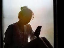Muchacha que usa el teléfono, sentándose en la ventana fotografía de archivo