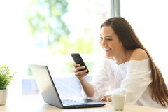 Muchacha que usa el teléfono y el ordenador portátil en casa Fotografía de archivo