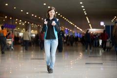 Muchacha que usa el teléfono celular en aeropuerto Imagen de archivo