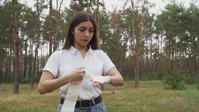 Muchacha que usa el vendaje elástico de estirar metrajes
