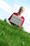 Muchacha que usa la computadora portátil al aire libre Foto de archivo libre de regalías