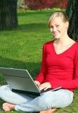 Muchacha que usa la computadora portátil al aire libre Fotos de archivo libres de regalías