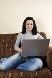 Muchacha que usa la computadora portátil en su sofá Fotos de archivo libres de regalías