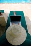 Muchacha que usa la computadora portátil mientras que se relaja Imagen de archivo
