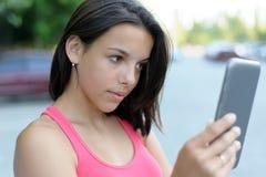 Muchacha que usa la tableta al aire libre Imagen de archivo libre de regalías