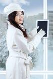 Muchacha que usa la tableta digital cerca de la ventana Fotografía de archivo libre de regalías