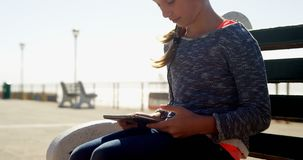Muchacha que usa la tableta digital en la playa 4k almacen de metraje de vídeo