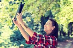 muchacha que usa la tableta digital que toma la imagen de sí misma imagen de archivo
