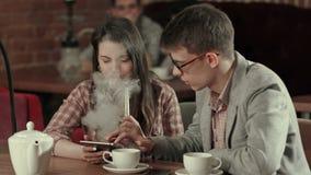 Muchacha que usa la tableta digital y al hombre que fuman mientras que mira la tableta almacen de metraje de vídeo