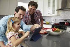Muchacha que usa la tableta en la cocina con los padres masculinos, cierre para arriba imagen de archivo libre de regalías