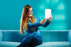 Muchacha que usa la tableta que toma a imagen de sí misma color azul Imagen de archivo libre de regalías