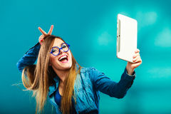 Muchacha que usa la tableta que toma a imagen de sí misma color azul Foto de archivo libre de regalías