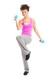Mujer joven que ejercita con pesas de gimnasia Fotografía de archivo libre de regalías