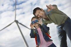 Muchacha que usa los prismáticos con el padre At Wind Farm Fotos de archivo libres de regalías