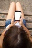 Muchacha que usa smartphone con la pantalla en blanco grande Imagen de archivo