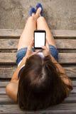 Muchacha que usa smartphone con la pantalla en blanco grande Fotos de archivo
