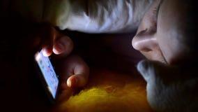 Muchacha que usa smartphone en una cama en sitio oscuro metrajes