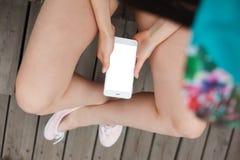 Muchacha que usa smartphone moderno grande del phablet con la pantalla en blanco Fotos de archivo libres de regalías