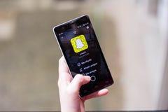 Muchacha que usa Snapchat Fotos de archivo