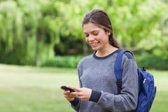 Muchacha que usa su teléfono móvil mientras que recibe un texto Imagen de archivo libre de regalías
