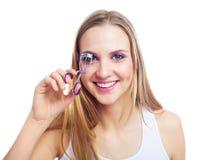 Muchacha que usa un bigudí de la pestaña Imagen de archivo