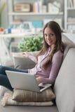Muchacha que usa un ordenador portátil en casa Imagenes de archivo