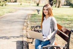 Muchacha que usa un ordenador portátil en un banco en parque Fotografía de archivo libre de regalías