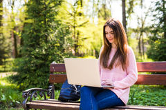 Muchacha que usa un ordenador portátil en un banco en parque de la universidad Fotografía de archivo libre de regalías