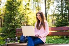 Muchacha que usa un ordenador portátil en un banco en parque de la universidad Imagen de archivo