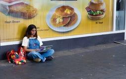 Muchacha que usa un ordenador portátil que se sienta en la calle Imagen de archivo