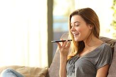 Muchacha que usa un reconocimiento vocal elegante del teléfono Imagen de archivo