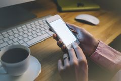 Muchacha que usa un smartphone con una pantalla de visualización en blanco limpia en atmósfera de oficina de negocios en el tecla imágenes de archivo libres de regalías